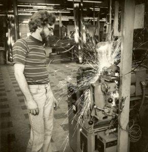 Man standing next to machine spraying sparks